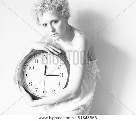 Scrawny girl with big clock in hands, b/w photo.