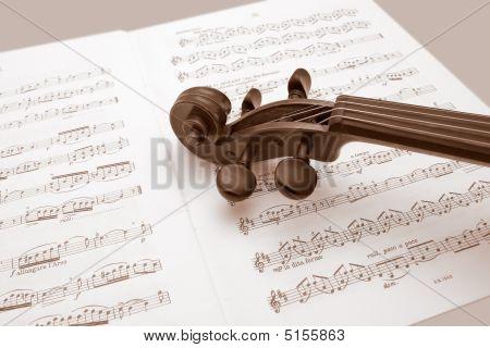 Vintage Violin Resting Over Music Scores