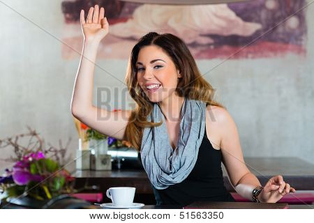 Young woman in a cafe or restaurant, she beckons to someone, perhaps she would like to pay the Bill