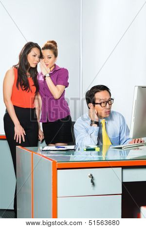 Asian Women or employee s tattle or whisper about colleague or man, bullying him in the office