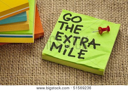 go the extra mile  - motivational reminder or procrastination concept  - handwriting on sticky note - handwriting on sticky note poster