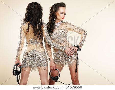 Fete. Clubbing. Two Women In Shiny Silver Dresses With Rhinestones