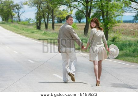 Happy Couple Walking By Rural Road