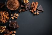 Black and milk chocolate cocoa powder nuts sweets spices and brown sugar on a black background food concept poster