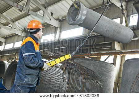 worker hoisting concrete pipe tube at production workshop plant