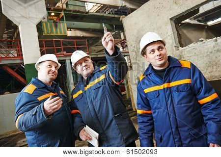 three industrial engineer chief discussing enterprise development in house-building plant
