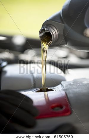 New oil being poured into a car during its regular service poster