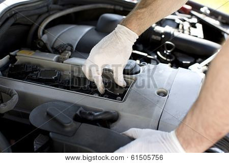 Car mechanic changing spark plugs