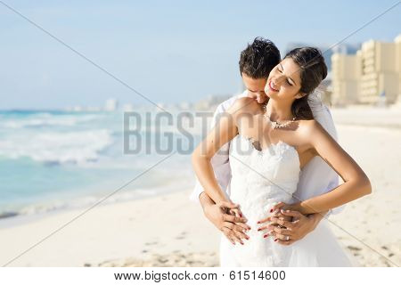 Newlyweds  sharing a romantic moment at the beach of Cancun