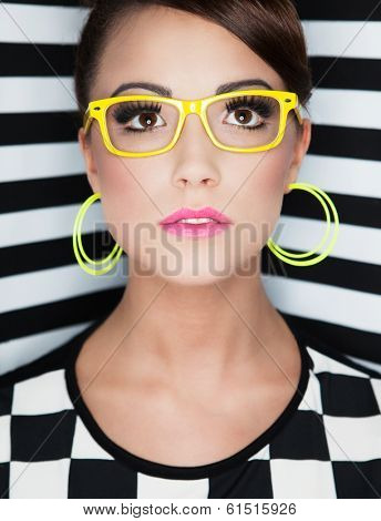 Attractive young woman wearing glasses on stripy background, beauty and fashion concept