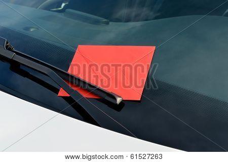 letter under a windshield wiper