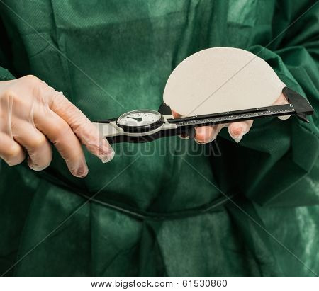 Plastic surgeon hands measuring silicon breast implants with calliper