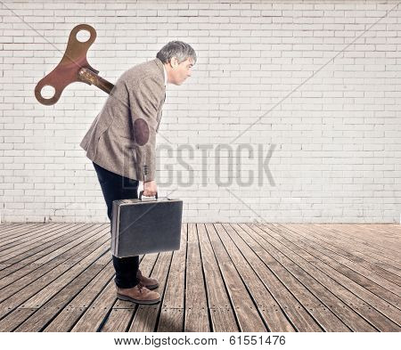 businessman with a wind up key in his back