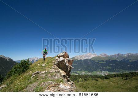 Mountain biker riding downhill in Swiss Alps in Graub?nden region poster