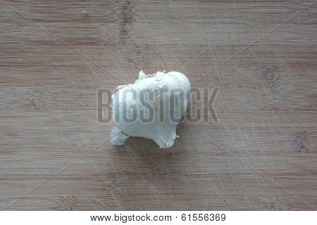 A Clove Of Garlic On Top Of A Cutting Board