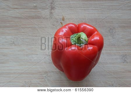 A Solo Red Pepper Standing On A Cutting Board