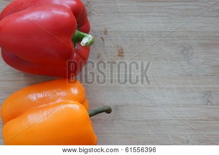 A Red And Orange Pepper On A Wooden Cutting Board