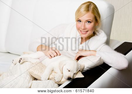 Woman sitting on the white leather sofa with sleeping on the pillow white puppy poster
