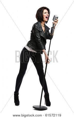 Full-length portrait of rock musician wearing leather jacket and keeping static microphone, isolated on white. Concept of rock music and rave