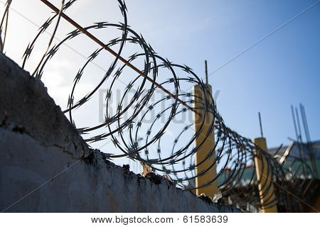 Barbed Wire On Top Of A Old Wall