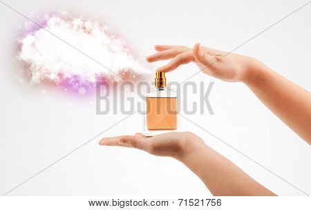 close up of woman hands spraying colorful cloud from beautiful perfume bottle