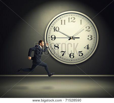 smiley running businessman and big white clock in dark room