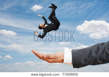 big palm catching small frightened businessman over blue sky