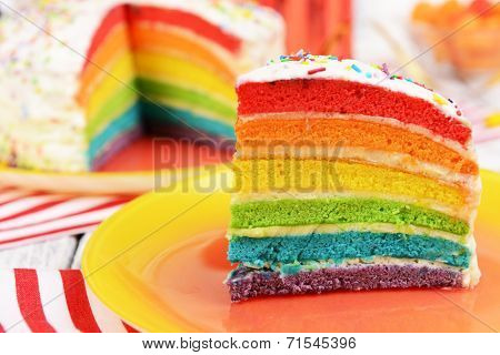 Delicious rainbow cake on plate on table on bright background poster