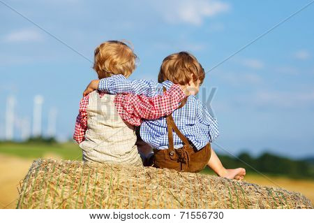 Two Little Children And Friends Sitting On Hay Stack
