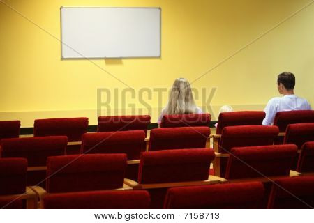 family in empty presentation hall is waiting start of showtime