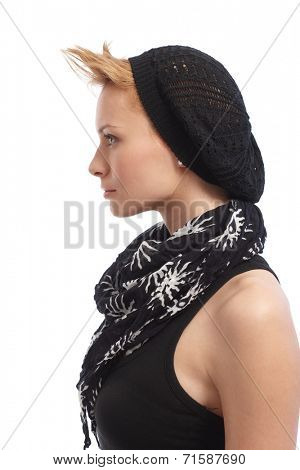 Profile of trendy young woman in sleeveless top, scarf and cap.