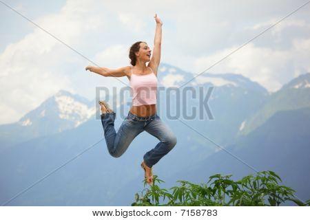 beautiful joyful woman is jumping. mountains behind her.