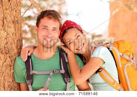 Hiking young couple portrait of happy hikers in Bryce Canyon walking smiling happy together. Multiracial couple, young Asian woman and Caucasian man in love, Bryce Canyon National Park landscape, Utah