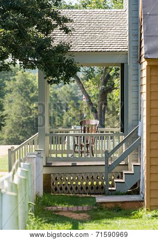 Wooden Rocking Chair On Porch Of Old House