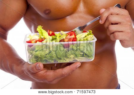 Close-up of a muscular man holding a bowl of fresh salad on a white background