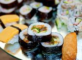 plate of rice sushi rolls stacked on a metal tray poster