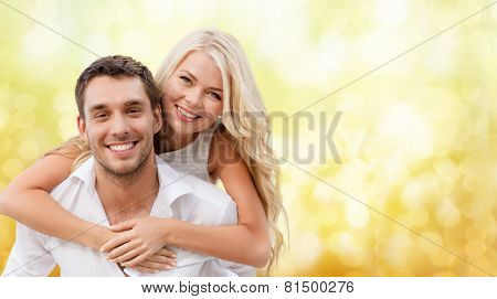 summer holiday, vacation, dating and love concept - happy couple having fun over yellow lights background