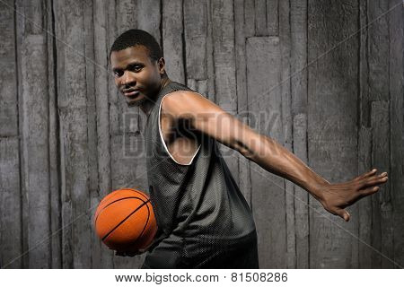 Afro-american young muscular male basketball player holding ball against grunge background and looking at camera poster