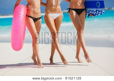 Three beautiful young women on the beach in a bikini.