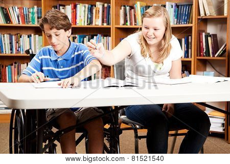 Teen boy and girl goofing around in the library.  The boy is disabled in a wheelchair.