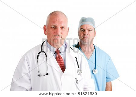 Mature doctor and younger, surgical intern.  Medical team with serious expressions.  Isolated on white.