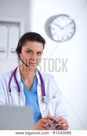 Doctor wearing headset sitting behind a desk with laptop over grey background
