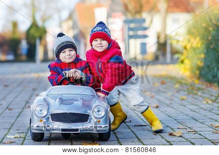 Two Happy Sibling Boys Playing With Big Old Toy Car, Outdoors