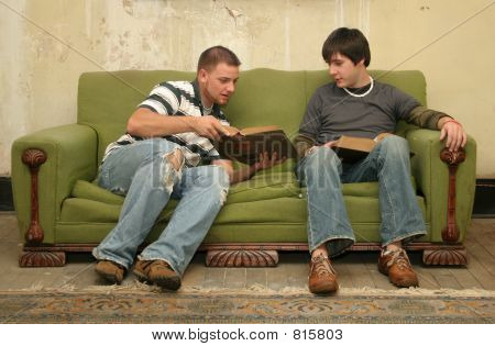 Two college men studying on old couch, old house. poster