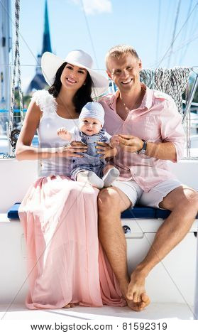 Young family on a sailing boat. Mother, father and a baby.