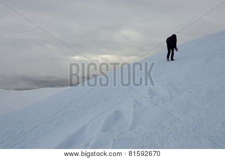 Lonely photographer with tripod making winter trekking on Gimba mountain during great snow storm ,Transcarpathianm, Western Ukraine poster