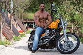 Biker Man Bodybuilder Sits On A Bike poster