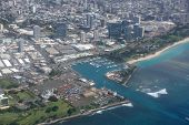 Aerial view of Kewalo Basin Harbor Kakaako Ala Moana Beach park in Honolulu with mall and Condo towers surrounding on a beautiful day in Oahu Hawaii. poster