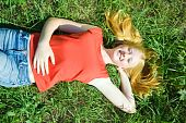 Carroty teenager girl lying at meadow grass poster
