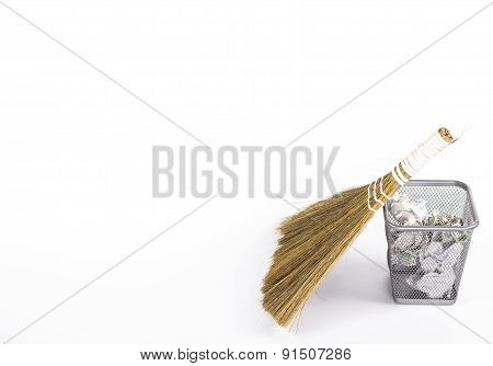isolated besom and wastebasket with white waste paper